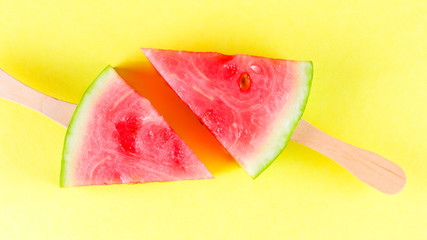 Slices of watermelon on stick on yellow background. Ice cream of watermelon on colored background....