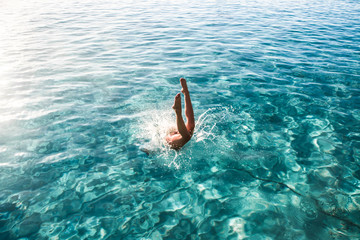 woman diving on body of water