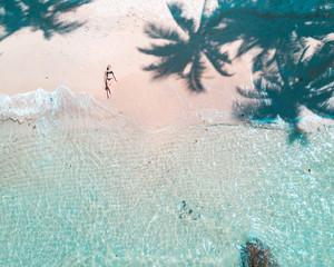 woman in bikini lying on seashore in aerial photography