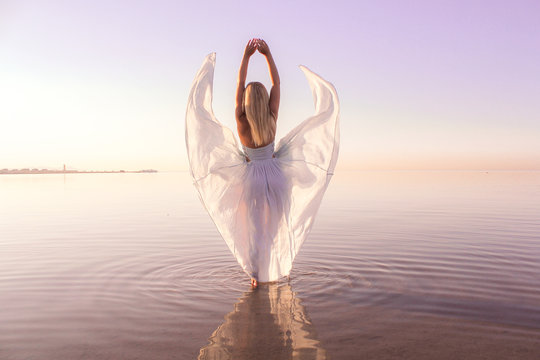 woman in white dress standing in body of water