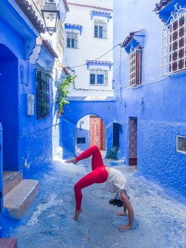 woman in white shirt and red pants doing yoga position in street during daytime