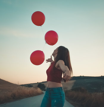 woman reaching for balloons during daytime