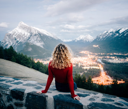 woman sitting overlooking city and mountains