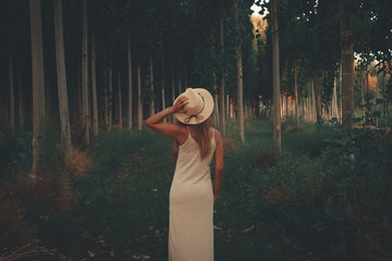 woman standing on forest while holding her hat