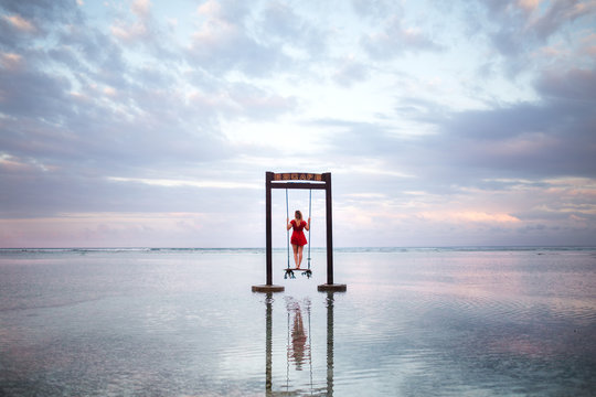 woman standing on swing surrounded with waters during daytime