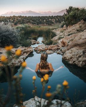 woman submerge on water between rocks