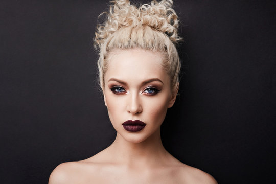 Sexy naked young woman with dark red full lips and with beautiful blue eyes with blond curly hair and with bright makeup, isolate at black background