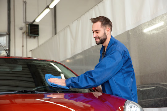 Worker cleaning automobile windshield with rag at car wash