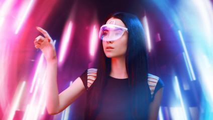 Wall Mural - Beautiful woman in futuristic 3d glasses with virtual projection over neon light background. Girl in glasses of virtual reality. Augmented reality, science, future technology, robots concept. VR.