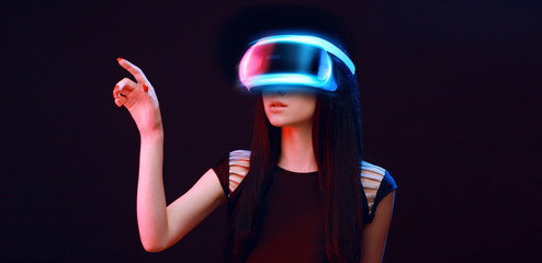 Wall Mural - Model young woman in glasses of virtual reality on dark background.. Augmented reality, science, future technology concept. VR. Futuristic 3d glasses with virtual projection. Neon light.