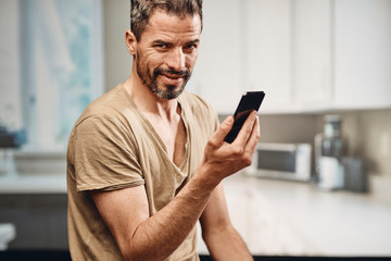 Handsome caucasian man texting and smiling in his kitchen