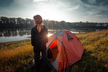 Young woman hiker stands near the tent and enjoys sunrise over the river