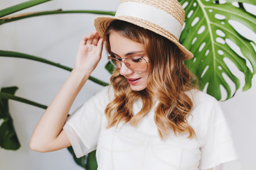 Wall Mural - Close-up indoor portrait of stunning blonde lady in elegant straw hat with ribbon. Charming curly girl in white shirt looking down while posing on plant background.