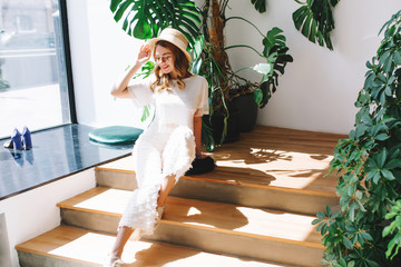 Wall Mural - Happy graceful girl in white pants relaxing on wooden steps near to big green plant in pot and looking down. Indoor portrait of stylish curly young woman sitting on stairs enjoys sunshine.