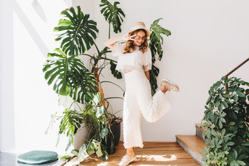 Wall Mural - Funny young lady in trendy pants standing on one leg and showing peace sign with smile. Laughing curly girl in stylish sneakers dancing beside big green flower and looking down.
