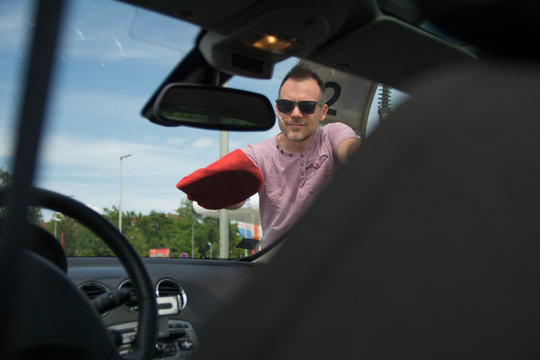 Man wiping windshield after a car wash