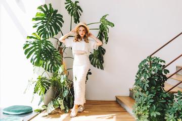 Wall Mural - Full-length portrait of dreamy girl in white sneakers and skirt standing with hands up in shadow of big green flower. Indoor photo of slim curly young woman in hat gracefully posing near plant.