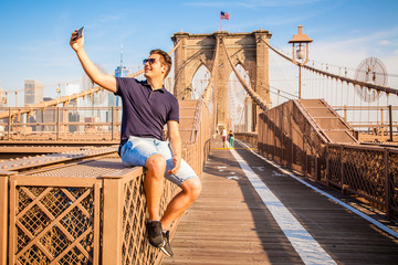 Tourist model taking a selfie on a Brooklyn Bridge