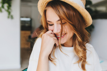 Wall Mural - Close-up photo of amazing happy girl with pale skin shy laughing and cover face with hand. Indoor portrait of ecstatic blonde young woman in hat smiling with eyes closed.