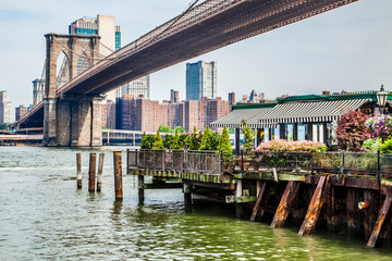 Amazing panorama view of New York city skyline and Brooklyn bridge with restaurant, skyscrapers and East River flowing during daytime in United States of America