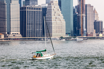 View of midtown Manhattan skyline and sailboat that is cruising on East River during sunny summer day in New York City, USA
