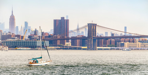 Panorama view of midtown Manhattan skyline, Brooklyn Bridge and sailboat that is cruising on East River during sunny summer day in New York City, USA