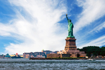 View of island of Liberty with statue of Liberty seen from the ferry in the Hudson river, symbol of the New York City, during sunny summer day