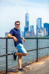 Handsome tourist model posing on a Governors Island with Manhattan in a background during sunny summer day in New York City, USA