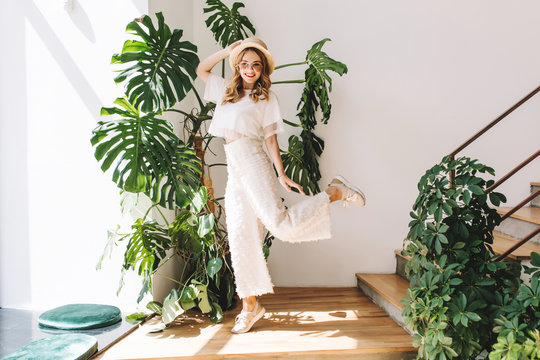 Ecstatic blonde girl in white pants funny dancing at home posing in front of big plant. Indoor portrait of jumping young woman in hat and glasses happy smiling next to stairs.