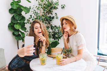 Wall Mural - Curly young woman in straw hat holding glass of icy cocktail while her long-haired friend making selfie. Indoor portrait of stylish blonde sisters resting together in restaurant and drinks juice.