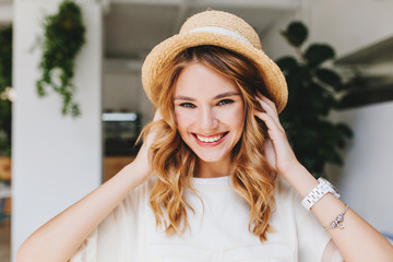 Wall Mural - Adorable laughing girl wearing silver bracelet and white wristwatch posing on blur background with pleasure. Close-up photo of glad young woman touching curly hair and playfully smiling.
