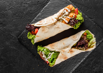 Tortilla wraps with grilled meat, fresh vegetables and salad on black stone background. Healthy snack or take-away lunch. Top view, flat lay