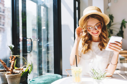 Smiling cute girl in straw hat relaxing in cafe beside glass door holding smartphone in hand. Indoor portrait of pretty blonde woman in glasses drinking cocktail alone and laughing enjoying good day.
