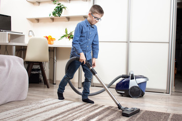 Fototapeta Odkurzanie dywanu w mieszkaniu przez chłopca ubranego w niebieską koszulę i spodnie jeansy. obraz