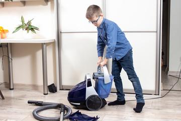 Fototapeta Chłopiec przygotowuje odkurzacz do sprzątania mieszkania.  Sprzątanie mieszkania. Chłopiec wkłada pojemnik z wodą do odkurzacza. obraz