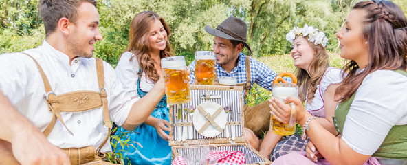 Five friends having fun on Bavarian RIver and clinking glasses with Oktoberfest beer