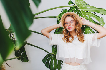 Wall Mural - Close-up portrait of lovely lady with serious face expression in white shirt posing with big green leaves. Indoor photo of elegant blonde girl in trendy glasses standing with hands up beside plant.