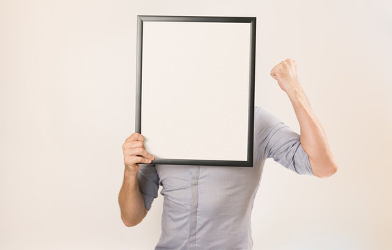 Unknown man wearing business shirt holding blank picture frame infront of his face