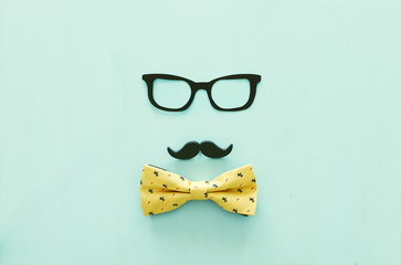 Father's day concept. Hipster glasses, mustache and bow tie on wooden background. top view, flat lay