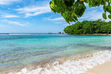 Beautiful sunny summer vacation day on tropical Caribbean island beach setting. Turquoise blue ocean water and white sand, lush trees all around, rock formations in background. Idyllic holiday scene.