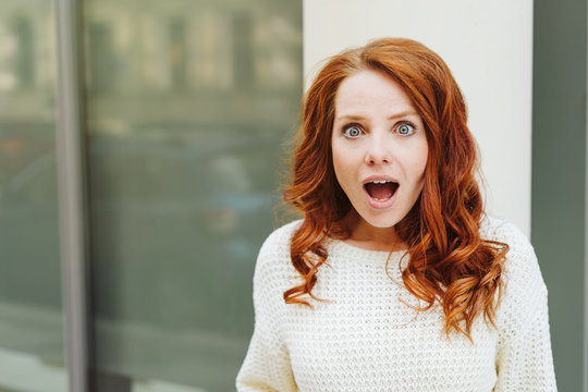 Shocked or amazed young redhead woman