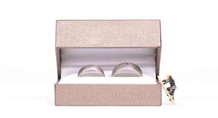 Wedding rings in box, small man climbing into the box