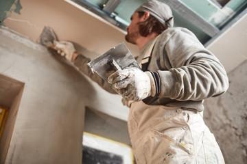 Workman plastering gypsum walls inside the house.