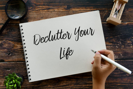 Top view of magnifying glass,sand clock,plant,pen with hand writing ' Declutter Your Life ' on notebook on wooden background.