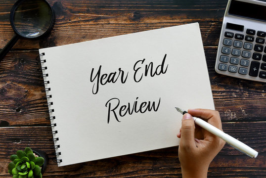 Top view of magnifying glass,calculator,plant,pen and hand writing ' Year End Review ' on a notebook on wooden background.