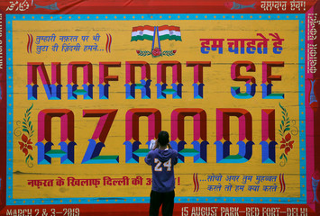 """A man takes a picture of an art installation at an event titled """"Artists Unite"""", during which various artists signed to register their concern against hate and intolerance, at a public park in New Delhi"""