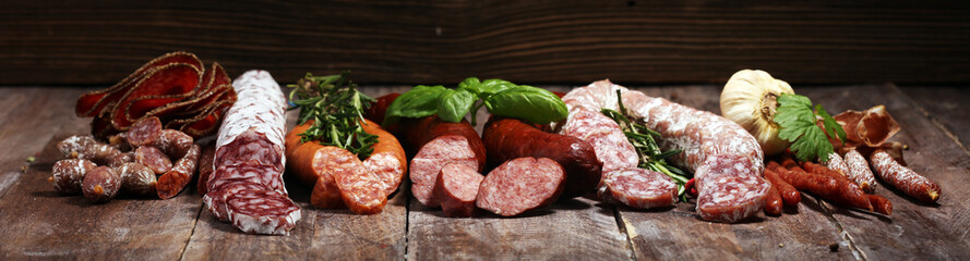 cold meat assortment with delicious salami and  fresh herbs . Variety of meat products including coppa and sausages Wall mural