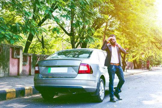Indian/asian young businessman using smart phone near car, outside view. selective focus