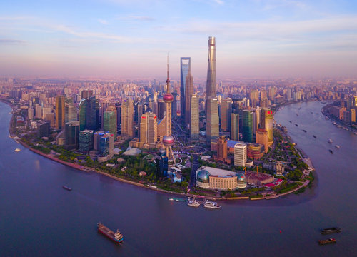 Aerial view of skyscraper and high-rise office buildings in Shanghai Downtown with Huangpu River, China. Financial district and business centers in smart city in Asia at sunset.