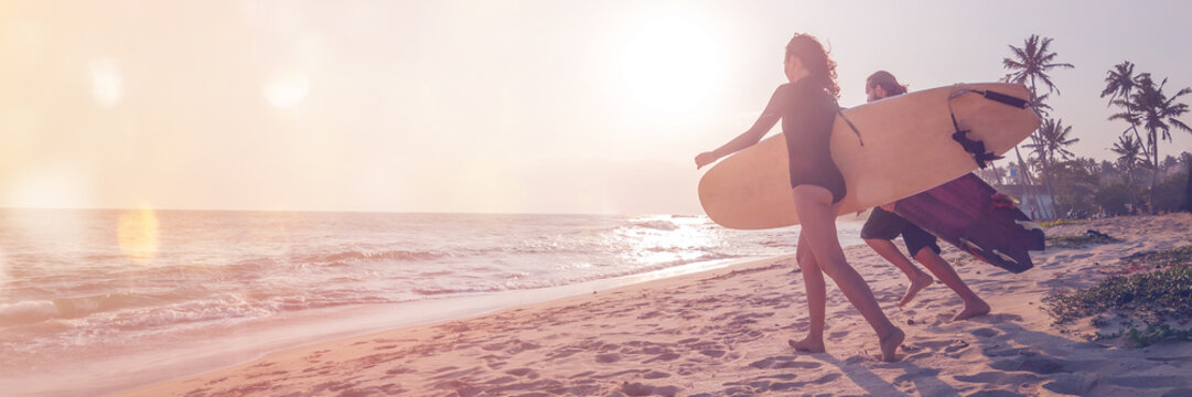 Young couple of happy smiling surfers run with surfboards on ocean coast, s panoramic banner header